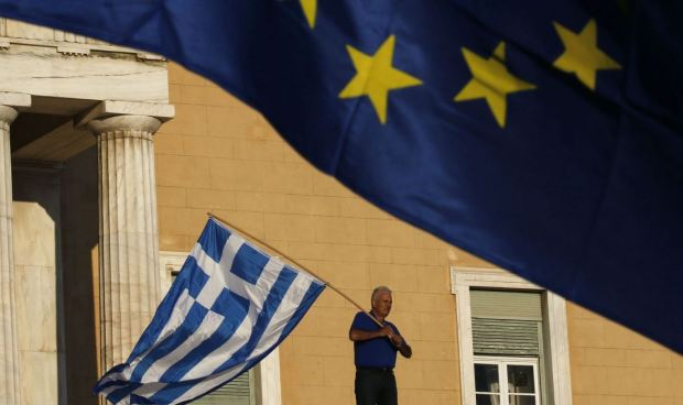Greek flag - man holding Euro flag up top