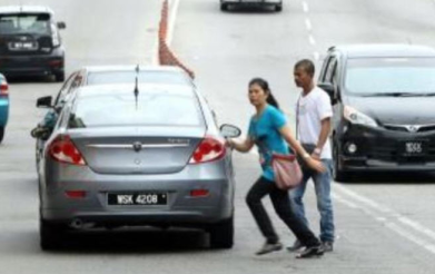 couple crossing street in Penang traffic