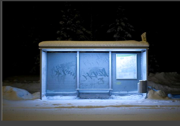 empty bus stop in snow night